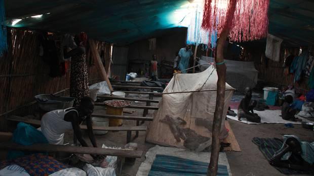 Kirche, Schule, Küche, Schlafraum: 20 Familien leben unter den Planen, mahlen Hirse, schlafen unter Netzen.