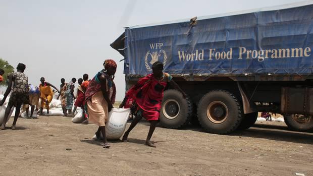 Von einer Sammelstelle schleppen Frauen 50-Kilo-Säcke mit Hirse nach Hause.