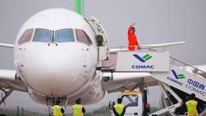 Jungfernflug in China: Ein Crewmitglied winkt nach erfolgreichem Flug mit dem Passagier-Jet