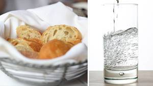 Ein Brotkorb und ein Glas Wasser stehen auf einem Tisch.