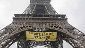 Ein gelbes Banner mit der Aufschrift Libertè, Egalité, Fraternité und dem Hashtag Resist von Greenpeace hängt am Eiffelturm