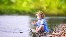 Ein kleines Mädchen sitzt am See