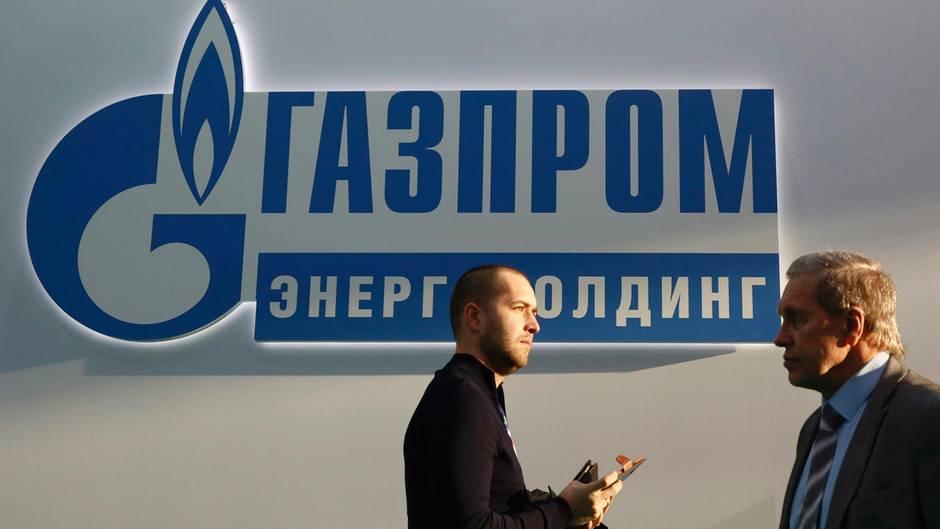 Teilnehmer einer Konferenz vor dem Logo des Energieversorgers Gazprom