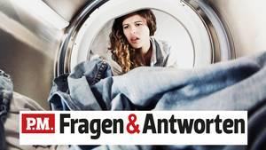 Eine Frau schaut entgeistert in ihre Waschmaschine