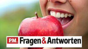 Eine Frau beißt lächelnd in einen Apfel