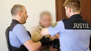 Der Angeklagte 37-Jährige wird beim Prozess in Leipzig in Handschellen vor Gericht geführt.