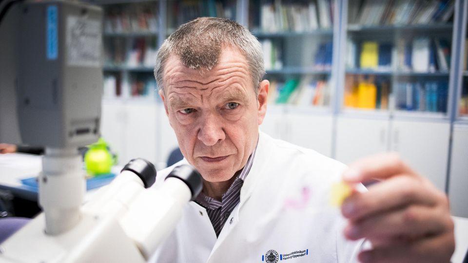 Klaus Püschel, ein Mann im weißen Kittel, sitzt vor einem Mikroskop. Er betrachtet eine Probe, die er in seiner linken Hand hält