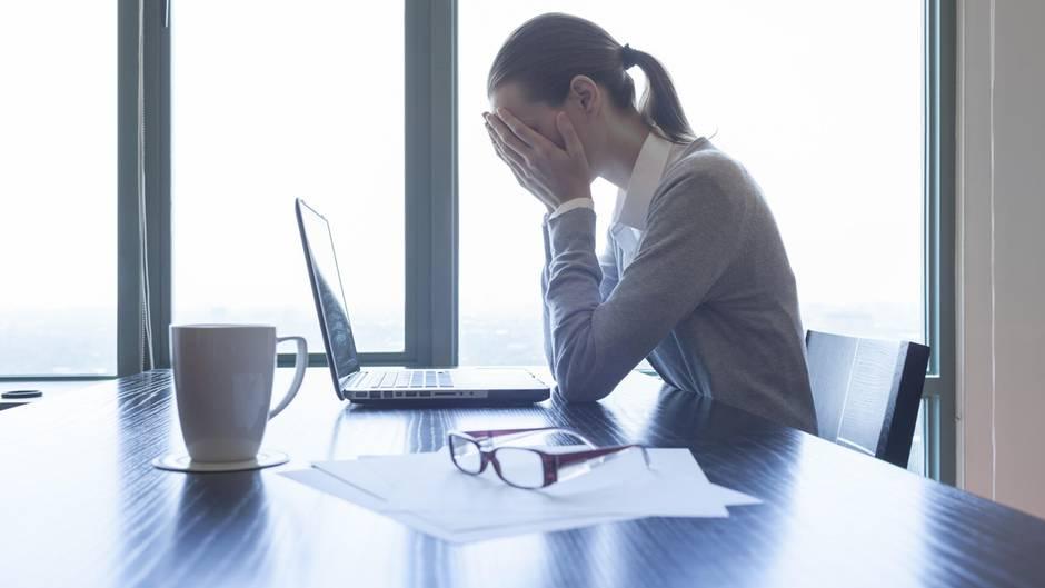Eine Frau schlägt vor dem Laptop die Hände vor dem Gesicht zusammen