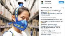 Eine junge chinesische Frau trägt einen aus einer Ikea-Tasche gefertigten Mundschutz