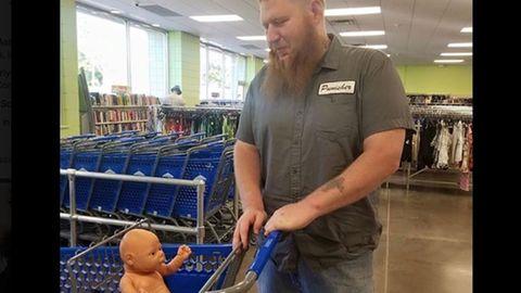 Vater geht mit Puppe im Einkaufswagen einkaufen