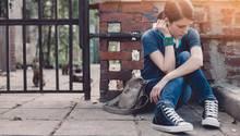 Ein weiblicher Teenager sitzt allein auf dem Bürgersteig
