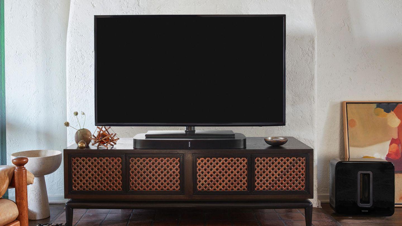 In einem schick eingerichteten Wohnzimmer steht ein Fernseher direkt auf der Sonos Playbar