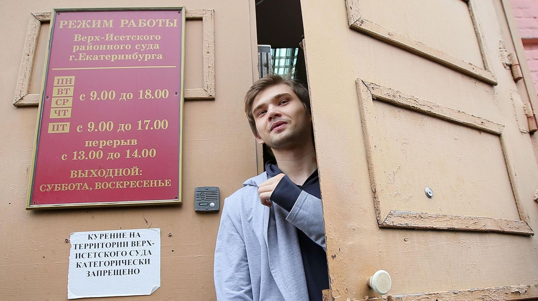 Ruslan Sokolowski, ein junger Mann mit dunkelblonden Haaren und hellgrauer Jacke, schaut aus der Tür des Gerichtsgebäudes