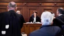 Eine Richterin in Robe sitzt auf der Richterbank aus dunklem Holz im Prozess wegen moderner Sklaverei in Brüssel