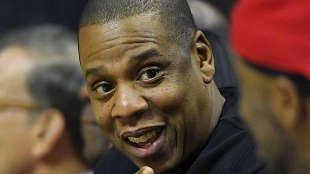 Jay-Z lächelt und zeigt mit seinem Finger auf einen Kollegen.