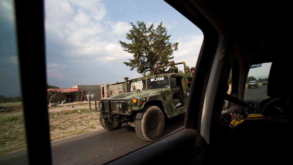 Durch das hintere Seitenfenster eines Autos ist ein Humvee des mexikanischen Militärs im Vorbeifahren zu sehen.