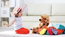 Kind sitzt auf dem Teppich und spielt Flugzeug