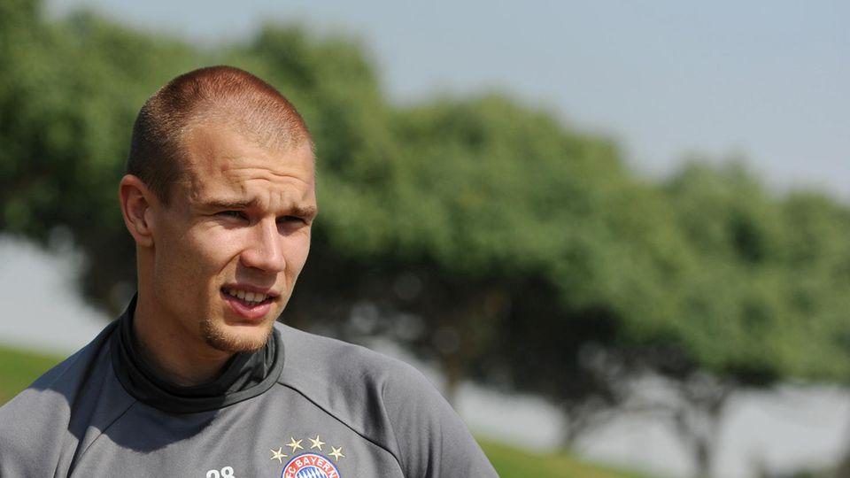 Im grauen Trainingspullover des FC Bayern München steht Holger Badstuber auf dem Platz und blinzelt in die Sonne.