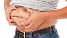 Ein Mann drückt mit seinen Händen den Bauchspeck zusammen. Laut der neuen Studie wird die Plauze bald Geschichte sein.