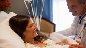 Ein Arzt sitzt am Bett einer frisch gewordenen Mutter, die ihren Säugling auf dem Arm hat