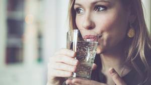 Frau trinkt Wasser mit Kohlensäure