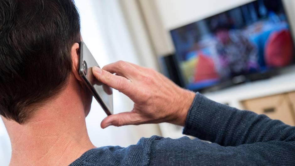 Ein Mann telefoniert in seinem Wohnzimmer. Forscher prüfen seit zwanzig Jahren, ob Handystrahlen Krebs verursachen können.