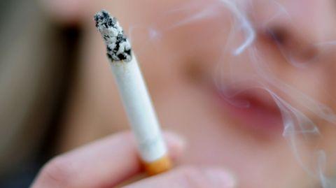 Eine junge Frau raucht eine Zigarette.