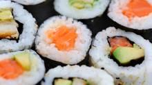 Sushi mit rohem Fisch liegt auf einem Teller.