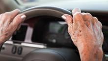 Hände einer alten Frau am Lenkrad eines Autos