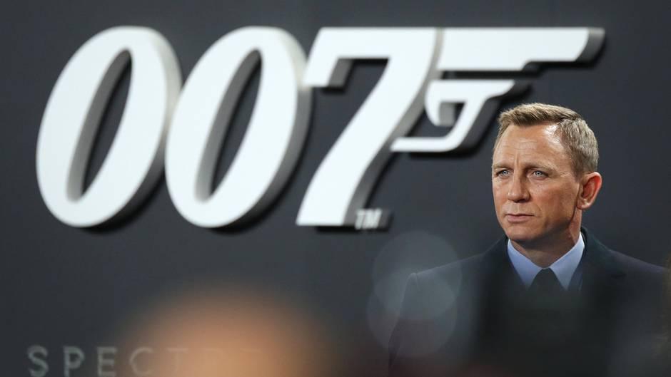 Schauspieler Daniel Craig steht im Anzug vor einer Wand mit großem 007-Logo. Er spielte in vier Filmen James Bond