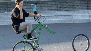 Radfahrer sitzt telefonierend auf Fahrrad und verliert Vorderrad