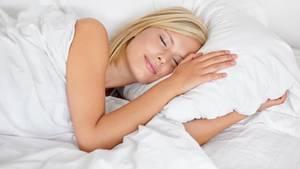 Eine Frau liegt im Bett und schläft