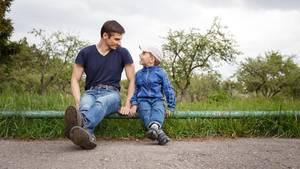Vater und Sohn sitzen nebeneinander am Straßenrand