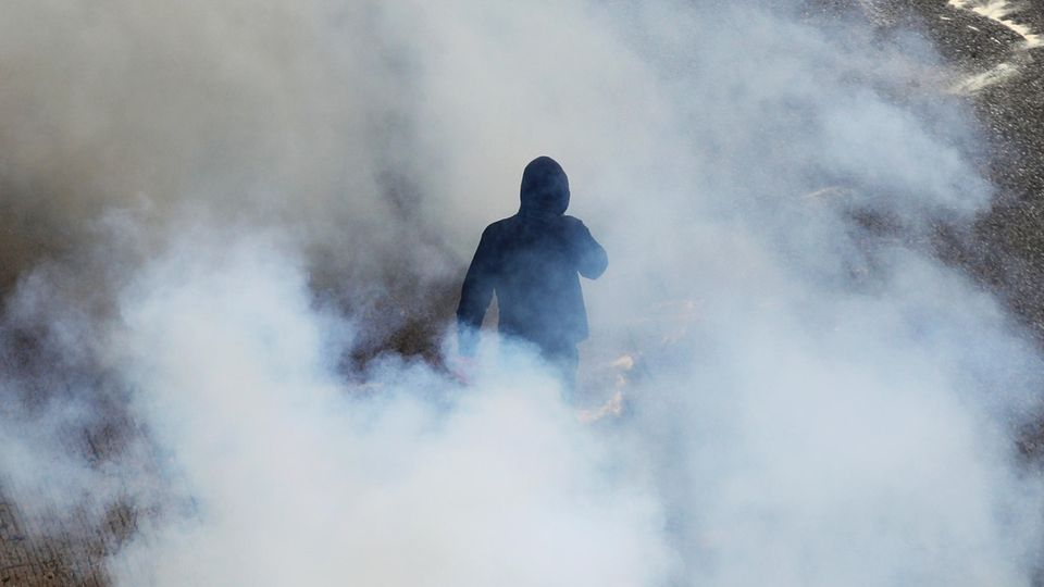 Ein Vermummter im schwarzen Hoodie umgeben von Rauchschwaden bei Demo in Athen