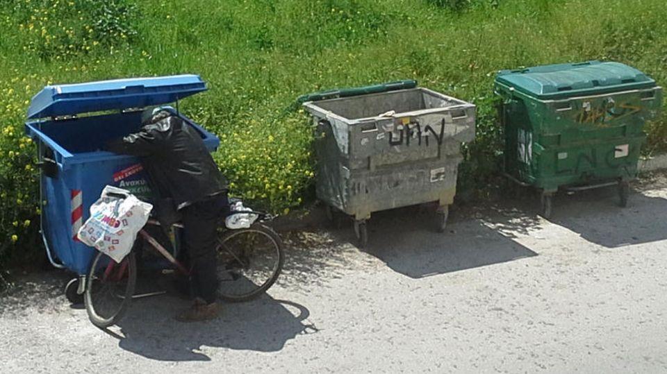 Mann sucht in Athen im Müll nach Essbarem