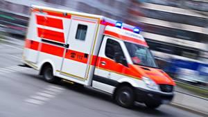 Ein Rettungswagen mit Blaulicht rast durch eine Stadt