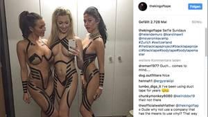 Drei Models, die nicht mehr als Klebeband an haben, posieren auf einem Spiegel-Selfie