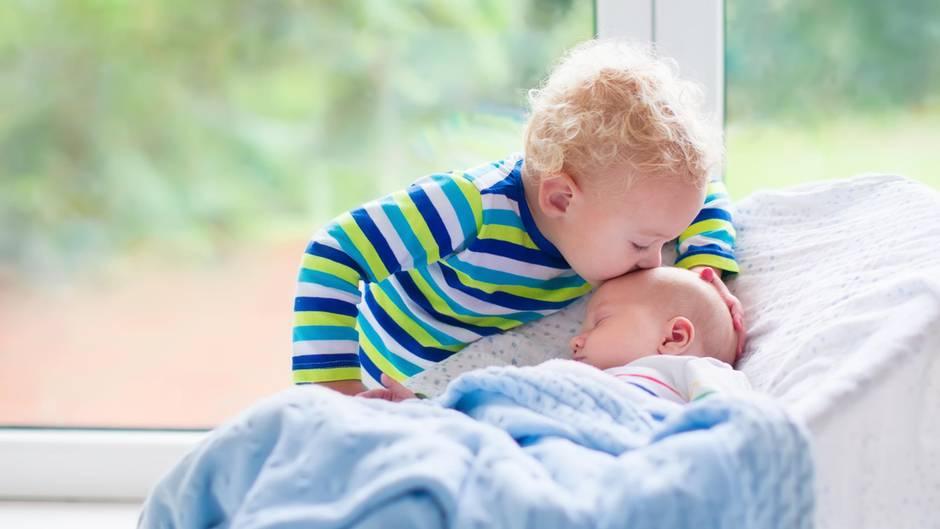 Großer Bruder küsst kleine Schwester auf Stirn