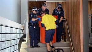 Polizisten bergen eine Mülltonne aus dem Wohnung Nr. 3 in einem Wohnhaus in Brisbane