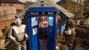 Ein Gartenhäuschen, das aussieht wie die TARDIS, mit zwei Robotern daneben