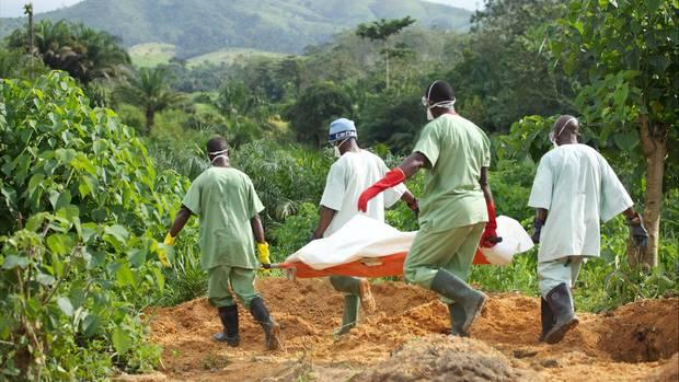 Mitglieder des roten Kreuz im Kongo tragen mit Ebola infizierten Leichnam