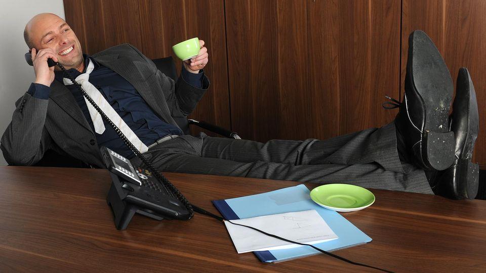 Ein Mann im Anzug telefoniert während er die Füße auf den Tisch legt