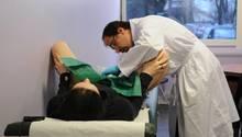 Ein Arzt untersucht die Vagina einer Frau