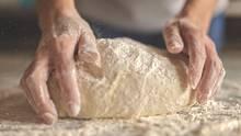 Ein Mann knetet Brotteig.