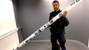Polizist hält Querlatte eines Tores, die von HSV-Fans geklaut worden war