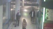 Eine Frau in einer rosa Jacke und zwei Männer gehen durch einen Gang mit Schaufenstern am Alexanderplatz in Berlin