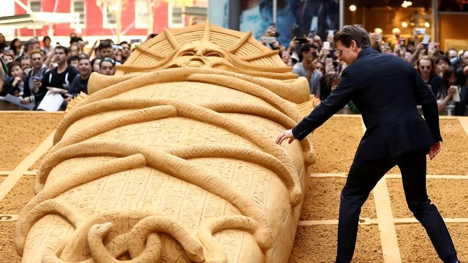 """Sydney, Australien. Fototermin mit Hollywoodstar: Tom Cruise greift vorsichtig an die Sandskultpur einer Mumie auf dem World Square. Cruise war zur Premiere seines neuen Films """"Die Mumie"""" in die Hauptstadt des Bundesstaates New South Wales gekommen. Der Streifen wird vom 8. Juni an auch in deutschen Kinos zu sehen sein."""