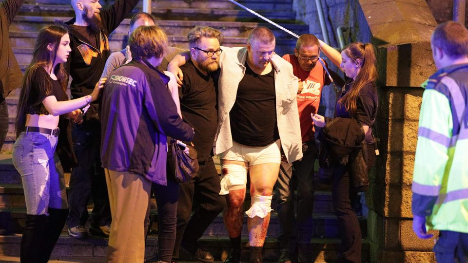 Ein verletzter Mann wird von Helfern vom Anschlagsort weggeführt
