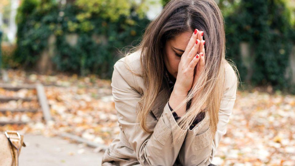 Frau sitzt vornübergebeugt mit den Händen vorm Gesicht
