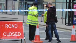 Polizisten sprechen nahe der Manchester Arena mit einem Passanten